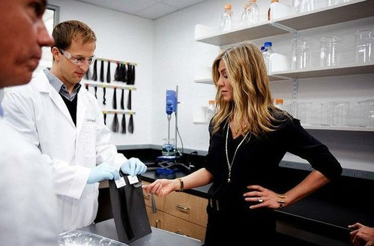David Puerto and Jennifer Aniston examine hair samples at a Living Proof product demonstration at Living Proof in Cambridge, Mass. Photo: Noel Federizo